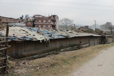 トタン屋根が飛ばないようにしてある建物。この中にも人が住んでいる。